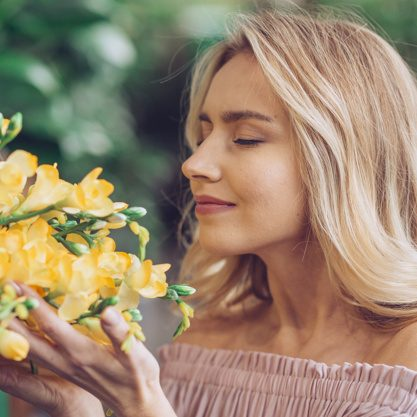 close-up-blonde-young-woman-smelling-freesia-flowers_23-2148049738